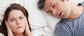 wife covering her ears as husband snores