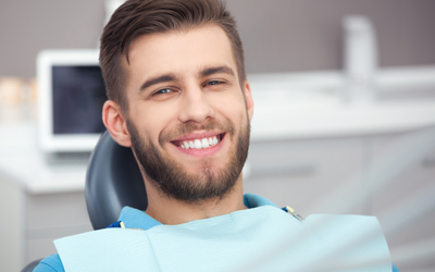 man sitting in dental chair smiling