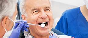 Elderly man receiving dental exam