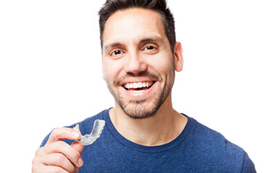 Man smiling holding Invisalign